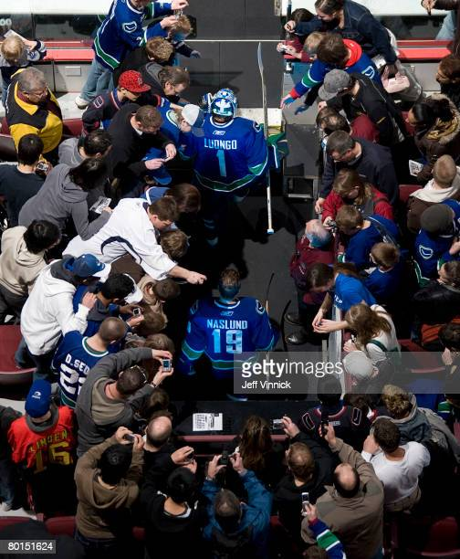 Roberto Luongo and Markus Naslund of the Vancouver Canucks are surrounded by fans as they walk onto the ice before their game against the Nashville...