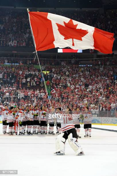 Roberto Luongo of Canada waves his national flag following his team's 3-2 overtime victory during the ice hockey men's gold medal game between USA...