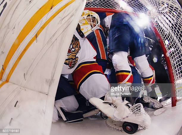 Roberto Luongo of the Florida Panthers grabs the puck as he is pushed into the net during the game against the New York Islanders in Game Four of the...
