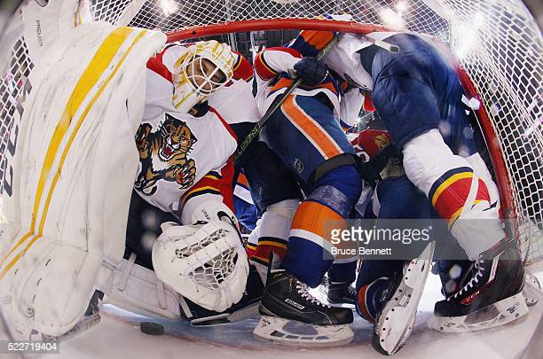 Roberto Luongo of the Florida Panthers is pushed aside as players from the Panthers and the New York Islanders converge in the crease during the...