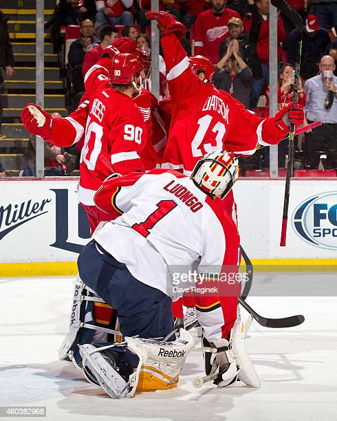 Roberto Luongo of the Florida Panthers looks up as Stephen Weiss Pavel Datsyuk and Tomas Tatar of the Detroit Red Wings congratulate teammate Riley...