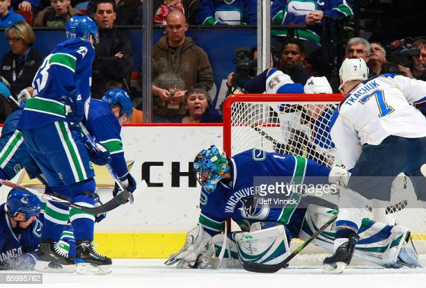 Roberto Luongo of the Vancouver Canucks gets his paddle down to make a save in front of teammates Alexander Edler Ryan Johnson and Shane O'Brien with...