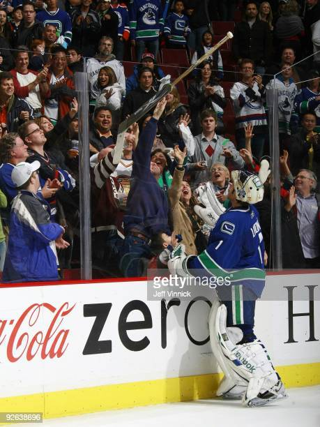 Roberto Luongo of the Vancouver Canucks gives his stick to a young fan during their game against the Edmonton Oilers at General Motors Place on...
