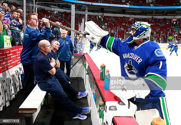 Roberto Luongo of the Vancouver Canucks hands his stick to trainer Brian Hamilton before their NHL game against the Phoenix Coyotes at Rogers Arena...
