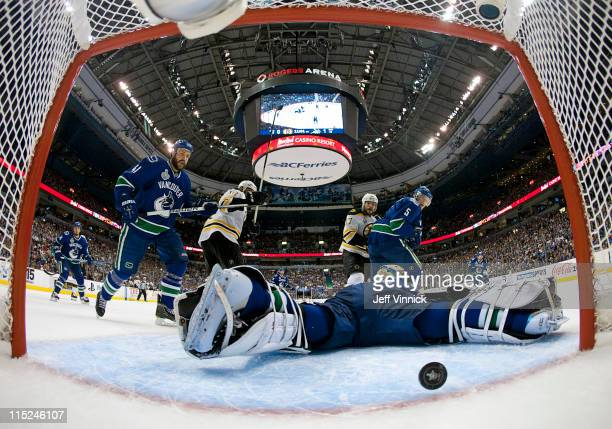 Roberto Luongo of the Vancouver Canucks has the puck go by him in the second period while teammates Christian Ehrhoff and Andrew Alberts look on...