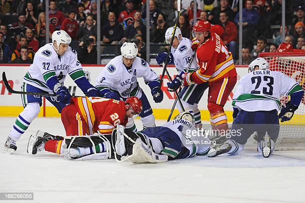 Roberto Luongo of the Vancouver Canucks holds the puck to stop a rebound from Curtis Glencross and Mikael Backlund of the Calgary Flames during an...