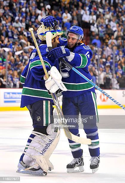 Roberto Luongo of the Vancouver Canucks is congratulated by teammate Alex Burrows after Luongo shut out the Boston Bruins 1-0 in game one of the 2011...
