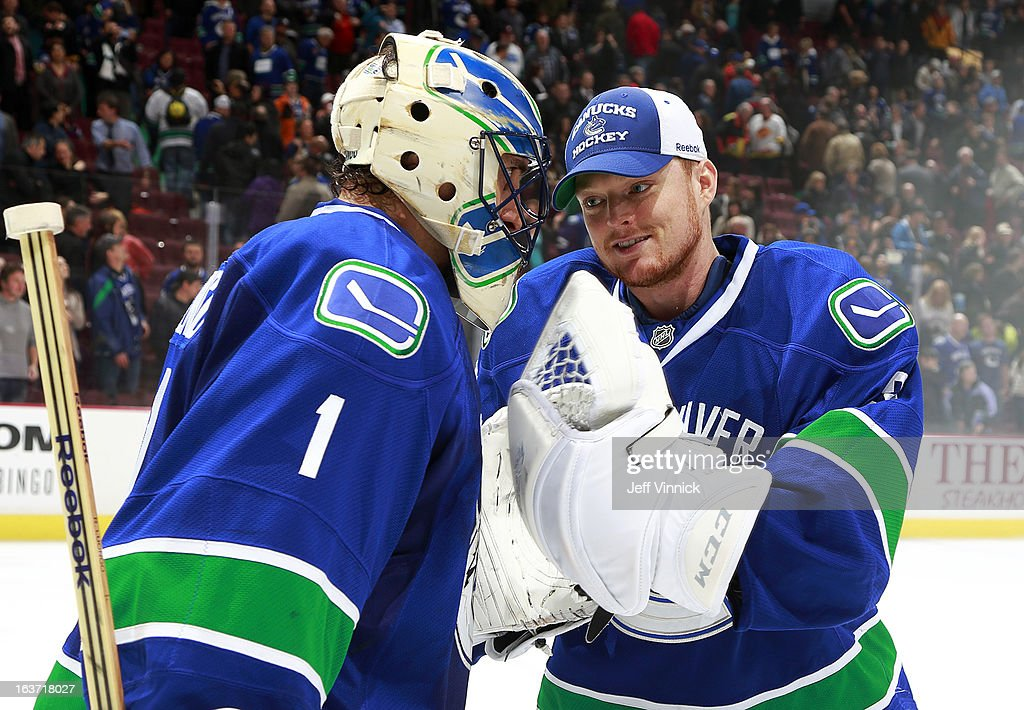Roberto Luongo #1 of the Vancouver Canucks is congratulated by teammate Cory Schneider #35 after an NHL game against the Nashville Predators at Rogers Arena March 14, 2013 in Vancouver, British Columbia, Canada. Vancouver won 7-4.