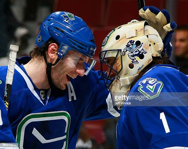 Roberto Luongo of the Vancouver Canucks is congratulated by teammate Ryan Kesler after their win at General Motors Place on December 10, 2009 in...