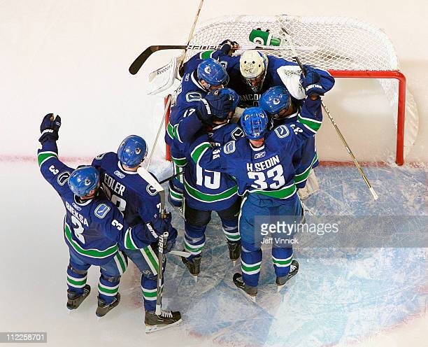 Roberto Luongo of the Vancouver Canucks is congratulated by teammates after their win in Game Two of the Western Conference Quarterfinals during the...