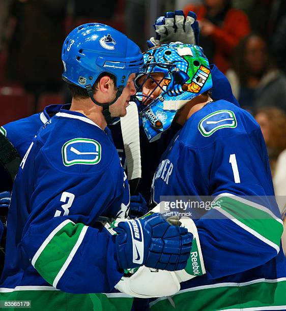 Roberto Luongo of the Vancouver Canucks is congratulated on his shutout by teammate Kevin Bieksa during their game against the Nashville Predators at...