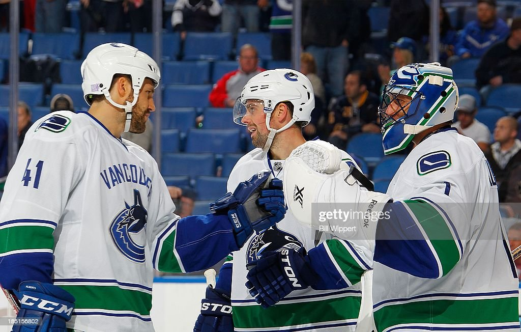Roberto Luongo #1 of the Vancouver Canucks is congratulationed by teammates Andrew Alberts #41 and Dan Hamhuis #2 following their 3-0 victory over the Buffalo Sabres on October 17, 2013 at the First Niagara Center in Buffalo, New York.