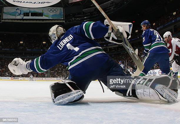 Roberto Luongo of the Vancouver Canucks makes a glove save as his teammate Mason Raymond and Stephane Yelle of the Colorado Avalanche look on during...