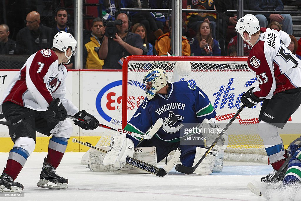 Roberto Luongo #1 of the Vancouver Canucks makes a save between Cody McLeod #55 and John Mitchell #7 of the Colorado Avalanche during their NHL game at Rogers Arena January 30, 2013 in Vancouver, British Columbia, Canada. Vancouver won 3-0.