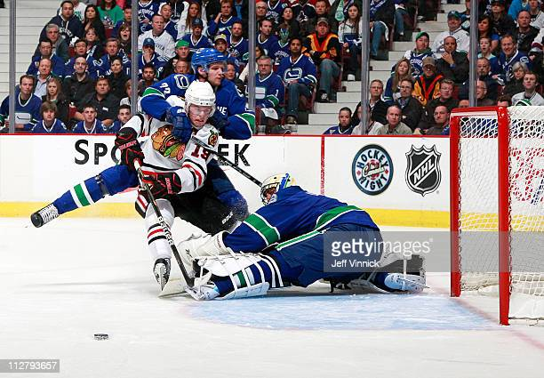 Roberto Luongo of the Vancouver Canucks makes a save on Jonathan Toews of the Chicago Blackhawks but Alexander Edler of the Vancouver Canucks draws a...