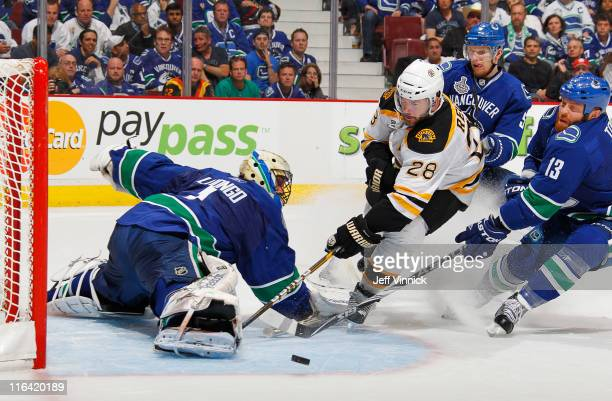 Roberto Luongo of the Vancouver Canucks makes a save on Mark Recchi of the Boston Bruins during Game Seven of 2011 NHL Stanley Cup Final between the...