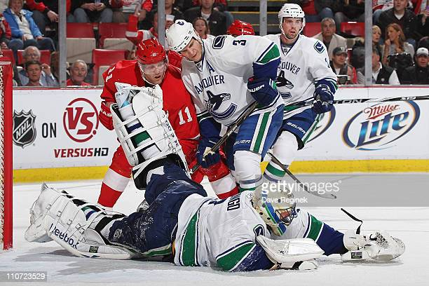 Roberto Luongo of the Vancouver Canucks makes a save while teammate Kevin Bieksa defends Dan Cleary of the Detroit Red Wings at Joe Louis Arena on...