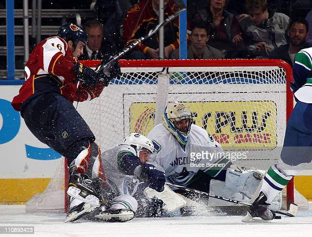 Roberto Luongo of the Vancouver Canucks makes the kick save in the third period as Andrew Ladd of the Atlanta Thrashers is tripped up in front at the...