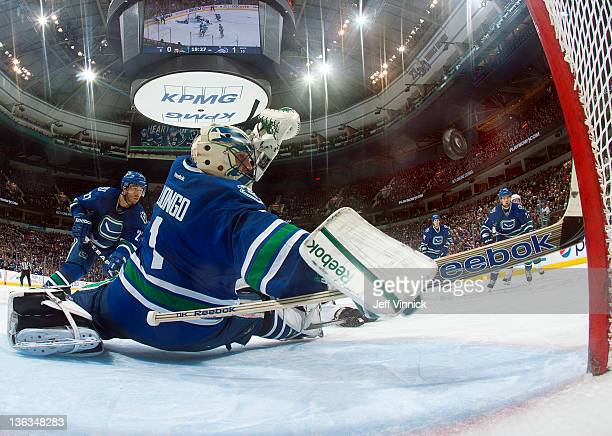 Roberto Luongo of the Vancouver Canucks rmakes a save against the San Jose Sharks during their NHL game at Rogers Arena January 2 2012 in Vancouver...
