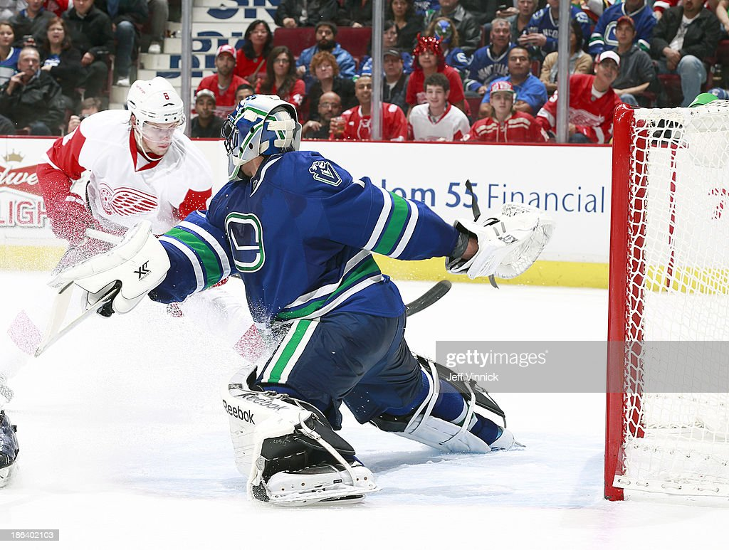 Roberto Luongo #1 of the Vancouver Canucks slides across the crease to make a save on Justin Abdelkader #8 of the Detroit Red Wings during their NHL game at Rogers Arena on October 30, 2013 in Vancouver, British Columbia, Canada. Detroit won 2-1.