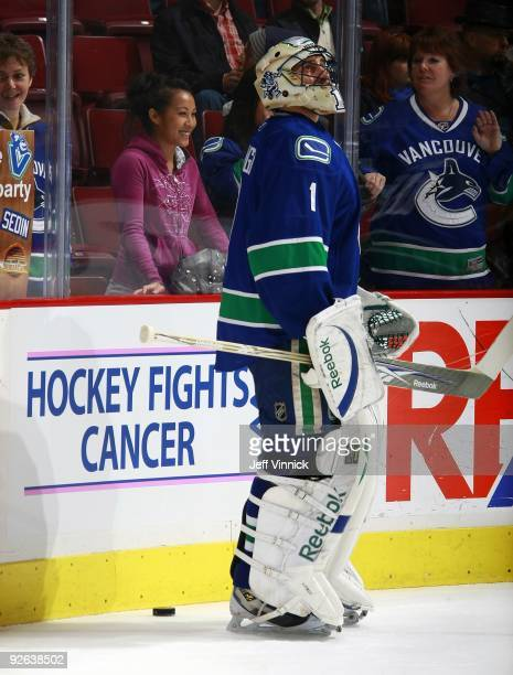 Roberto Luongo of the Vancouver Canucks stands by a Hockey Fights Cancer sign during their game against the Edmonton Oilers at General Motors Place...
