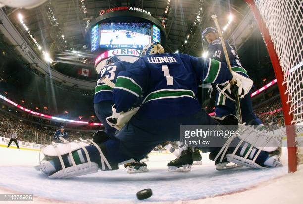 Roberto Luongo of the Vancouver Canucks stretches to his left after the puck caromed off the left post and across the crease to the right side wide...