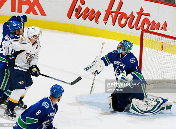 Roberto Luongo of the Vancouver Canucks watches the puck go high while teammate Willie Mitchell looks on and Kevin Bieksa checks J.P. Dumont of the...