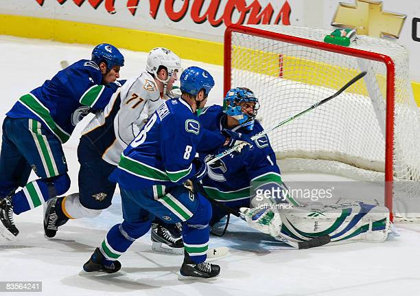 Roberto Luongo of the Vancouver Canucks watches the puck go wide after making a save while teammates Kevin Bieksa and Willie Mitchell check J.P....