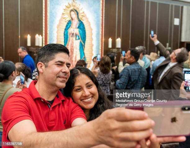 Roberto Magana, left, and his girlfriend Patricia Barajas, take a selfie in front of the mosaic artwork depicting the Virgin of Guadeloupe following...