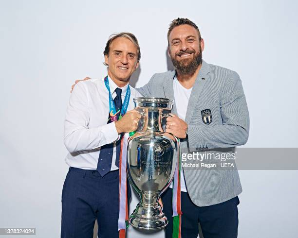 Roberto Mancini, Head Coach of Italy and Daniele De Rossi, Assistant Coach of Italy pose with The Henri Delaunay Trophy during an Italy Portrait...