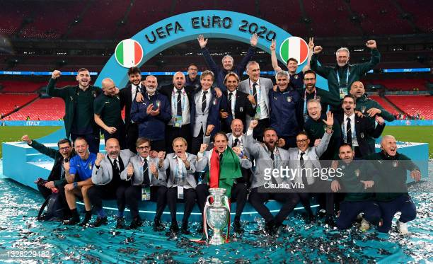 Roberto Mancini, Head Coach of Italy and the backroom staff celebrate with The Henri Delaunay Trophy following his team's victory in the UEFA Euro...