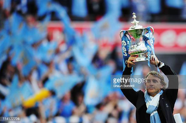 Roberto Mancini lifts the trophy after his Manchester City team wins the FA Cup sponsored by E.ON Final match between Manchester City and Stoke City...