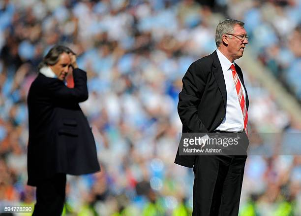 Roberto Mancini the head coach / manager of Manchester City and Sir Alex Ferguson the head coach / manager of Manchester United