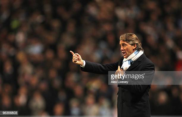 Roberto Mancini the manager of Manchester City gives instructions to his players during the Barclays Premier League match between Manchester City and...
