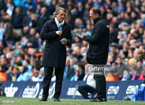 Roberto Mancini the manager of Manchester City talks with his assistant David Platt during the Barclays Premier League match between Manchester City...