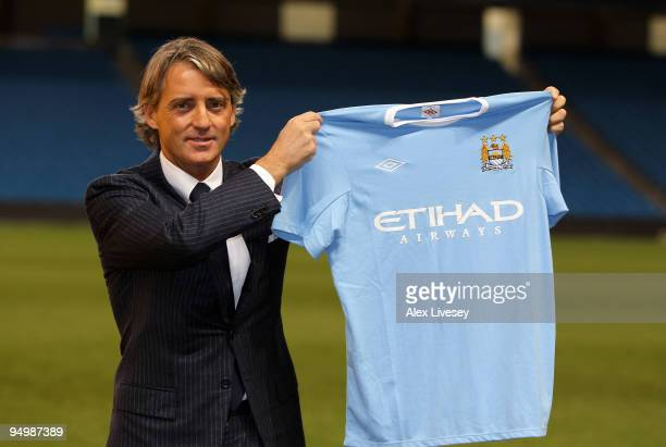Roberto Mancini the new manager of Manchester City holds up a Manchester City shirt during a photocall after a press conference held at the City of...