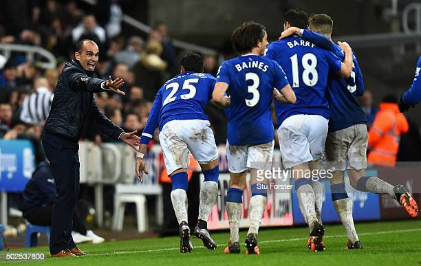 Roberto Martinez manager of Everton celebrates with players as Tom Cleverley scores their first goal during the Barclays Premier League match between...
