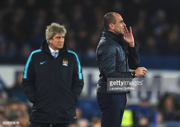 Roberto Martinez manager of Everton gives instructions with Manuel Pellegrini manager of Manchester City during the Capital One Cup Semi Final First...