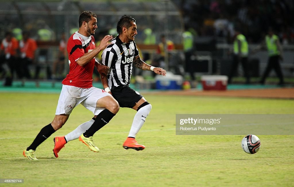 Roberto Maximilano Pereyra (R) of Juventus FC battles for the ball during the pre-season friendly match between Indonesia Selection All Star Team and Juventus FC at Gelora Bung Karno Stadium on August 6, 2014 in Jakarta, Indonesia. Juventus FC won the game 8-1.