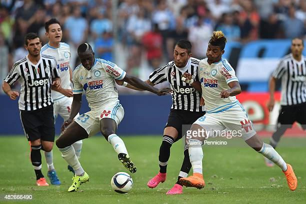Roberto Maximiliano Pereyra of Juventus FC is challenged by Mario Lemina and Benjamin Mendy of Olympique de Marseille during the preseason friendly...
