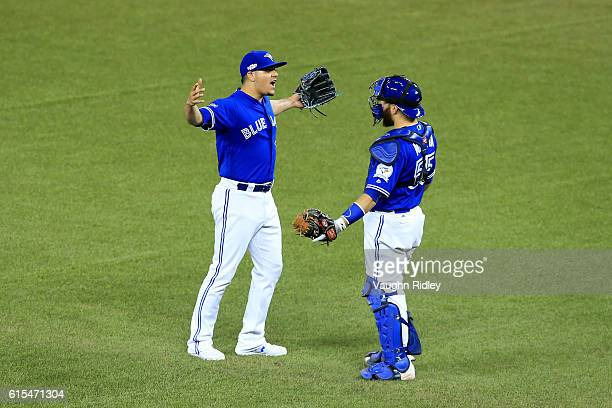 Roberto Osuna and Russell Martin of the Toronto Blue Jays celebrate after defeating the Cleveland Indians with a score of 5 to 1 in game four of the...