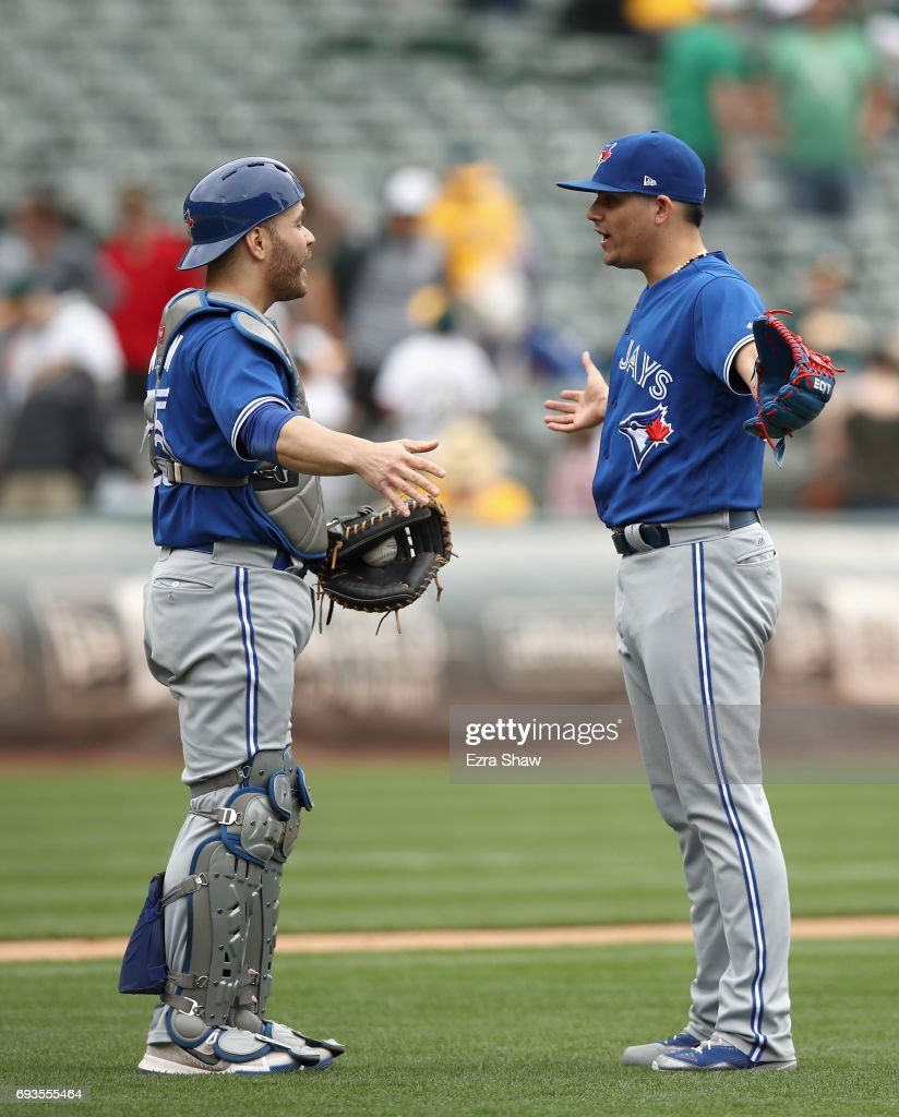 Roberto Osuna #54 and Russell Martin #55 of the Toronto Blue Jays celebrate after they beat the Oakland Athletics in ten innings at Oakland Alameda Coliseum on June 7, 2017 in Oakland, California.