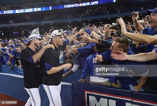 Roberto Osuna of the Toronto Blue Jays and Ryan Tepera celebrate with fans after winning the game and series in the tenth inning during MLB game...