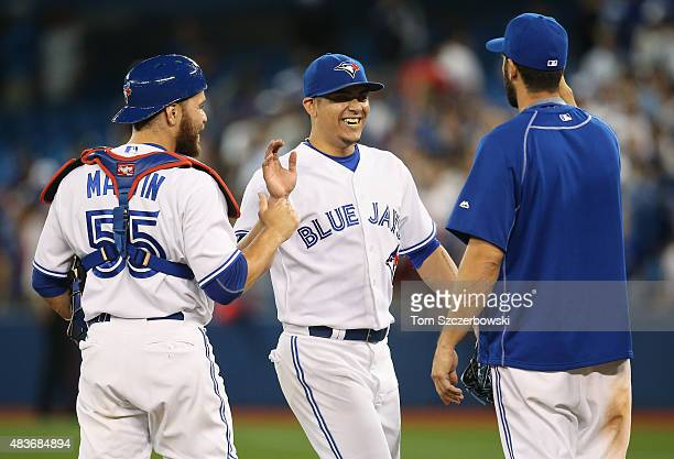 Roberto Osuna of the Toronto Blue Jays celebrates their victory with Russell Martin and Chris Colabello during MLB game action against the Oakland...
