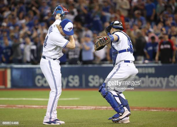 Roberto Osuna of the Toronto Blue Jays celebrates their victory with Russell Martin during MLB game action against the Texas Rangers at Rogers Centre...