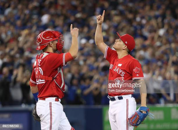Roberto Osuna of the Toronto Blue Jays celebrates their victory with Luke Maile during MLB game action against the New York Yankees at Rogers Centre...