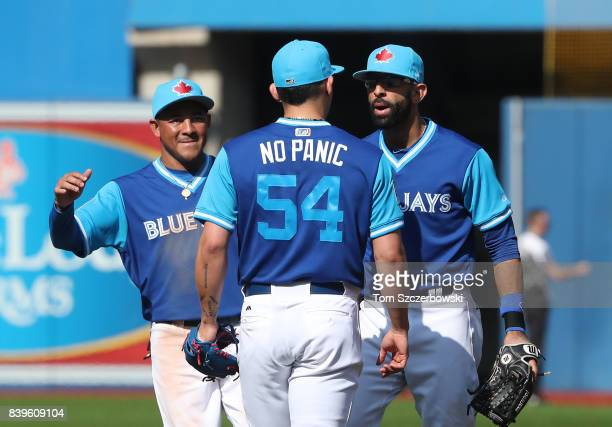 Roberto Osuna of the Toronto Blue Jays celebrates their victory with Jose Bautista and Ezequiel Carrera during MLB game action against the Minnesota...