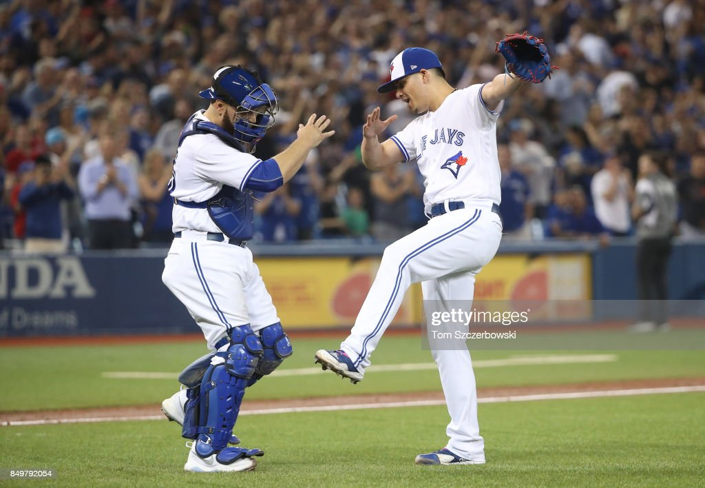 Roberto Osuna #54 of the Toronto Blue Jays celebrates their victory with Russell Martin #55 during MLB game action against the Kansas City Royals at Rogers Centre on September 19, 2017 in Toronto, Canada.
