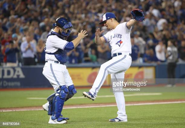 Roberto Osuna of the Toronto Blue Jays celebrates their victory with Russell Martin during MLB game action against the Kansas City Royals at Rogers...