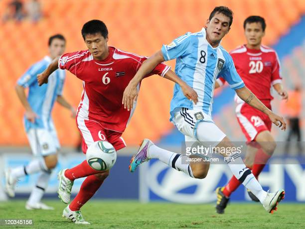 Roberto Pereyra of Argentina duels for the ball with Ri Il Jin of Korea DPR during the FIFA U20 World Cup Colombia 2011 group F match between...